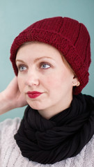 girl light skin in a marsala knitted cap with marsala lipstick, tender, against a background of a sky-colored wall or a minolta in a white sweater and a black scarf, close portrait