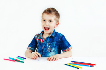 Young cute boy wearing a blue shirt with colored pencils on a white background. Concept idea