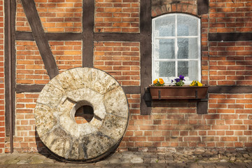 Fotobehang Molens Old millstone in front of half-timbered house