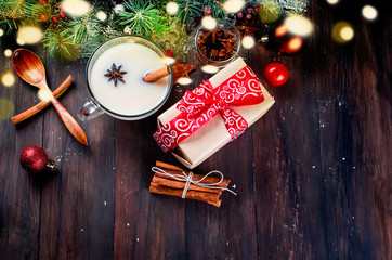 Cup of tea with milk and  cinnamon, fir, cones, cocoa in red cup  on the dark wooden background
