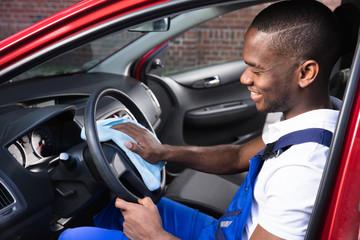 Male Worker Cleaning Steering Wheel