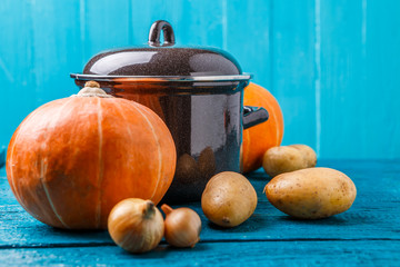 Photo of iron pot with lid, vegetables, potatoes, pumpkins, onions
