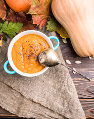 Picture from above of healthy pumpkin soup on linen fabric
