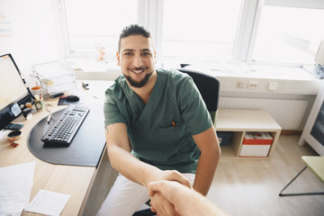 Portrait of smiling young male nurse shaking hands with doctor at office in hospital