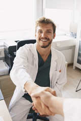 Portrait of smiling young male doctor shaking hands with nurse at office in hospital