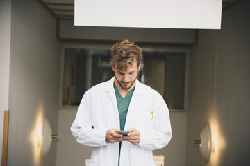 Young male doctor using mobile phone at hospital