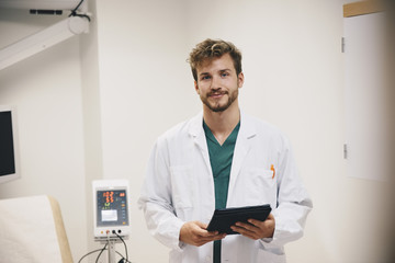 Portrait of confident male doctor standing with digital tablet at hospital