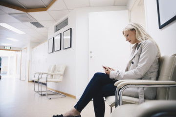 Side view of woman using smart phone while sitting on chair in hospital corridor