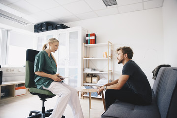 Female nurse talking with male patient in office