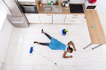 Unconscious Housewife Lying On Kitchen Floor