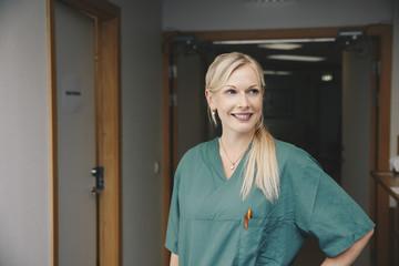 Smiling mid adult female nurse standing in hospital corridor