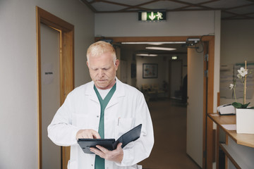 Mature doctor using digital tablet while standing in hospital corridor
