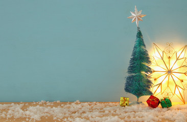 Image of christmas trees on snowy wooden table.