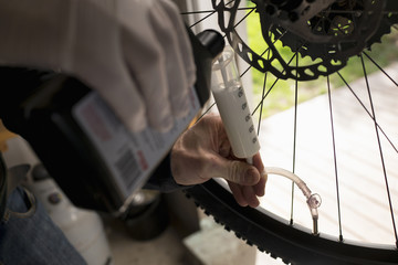 Cropped image of man putting chemical in tire