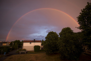 Idyllic view of rainbow over house by trees at dusk