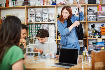 Young redhead technician standing with bag by female colleagues at workshop