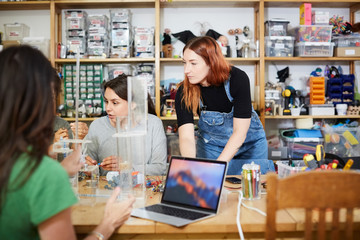 Young redhead technician standing by female coworkers at workshop