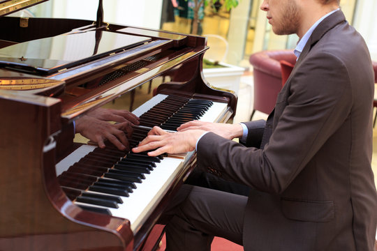 Handsome young men playing piano