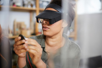 Female technician looking at electrical component through loupe in workshop