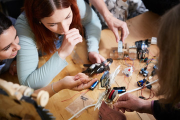 High angle view of female engineers making robot at table in workshop