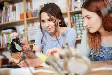 Young female technicians making model at table in workshop
