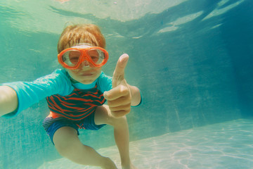happy boy swimming underwater with thumbs up