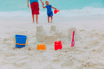 sand castle and toys, father with daugther play on beach