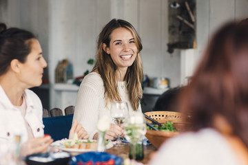 Happy young female friends enjoying at dining table during lunch party