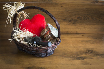 Valentines day background. Ratan basket full of bottle of red wine, two copper glasses and big, red, valentines heart