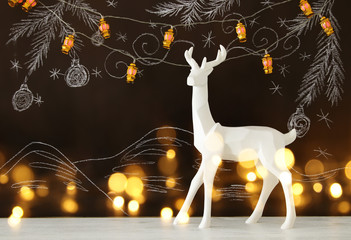 White reindeer on wooden table over chalkboard background with hand drawn chalk illustrations.