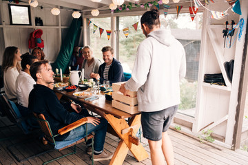 Young man holding crate while enjoying lunch party with friends in cottage