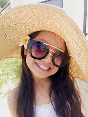 Asian long black hair girl is wearing black sunglasses, straw hat and white flower behind the right ear.