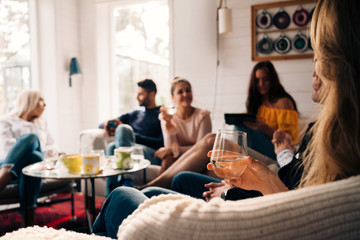 Woman holding glass while sitting with friends in cottage