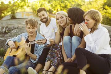 Man playing guitar while friends enjoying during summer