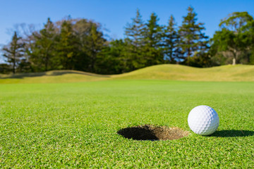 Golf Course where the turf is beautiful and Golf Ball on putting green. Golf is a sport to play on the turf