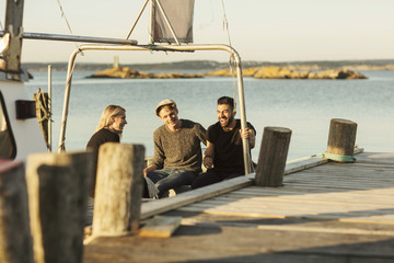 Friends sitting on moored boat