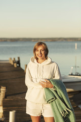 Portrait of smiling young woman holding blanket while standing at jetty