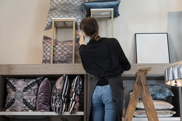 Rear view of young female entrepreneur standing on ladder while arranging cushion in rack at store