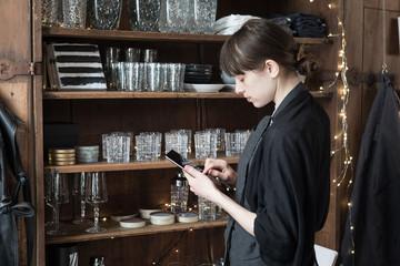 Side view of young female entrepreneur using digital tablet while standing by rack at store