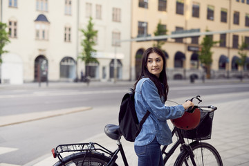 Mid adult woman looking away while walking with bicycle in city