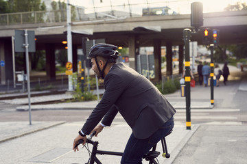 Side view of businessman cycling on street in city