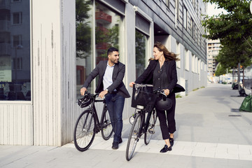 Full length of business coworkers walking with bicycles on sidewalk in city