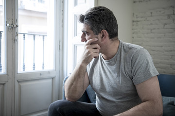 sad and worried man with grey hair sitting at home couch looking