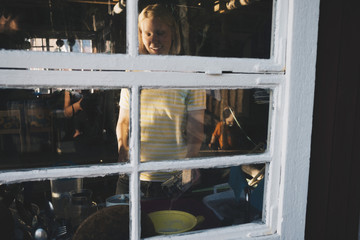 Smiling woman cooking food seen from glass window