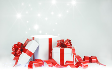 three christmas gift white box with red bow and ribbon on faded grey background with shining stars