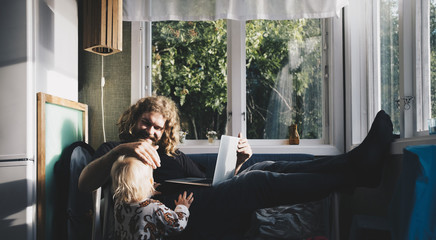 Father using laptop and talking to baby daughter