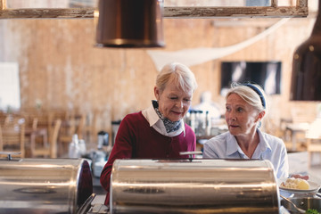 Senior female friends getting food from buffet counter at restaurant