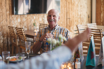 Smiling senior man looking at friend while sitting at table in restaurant