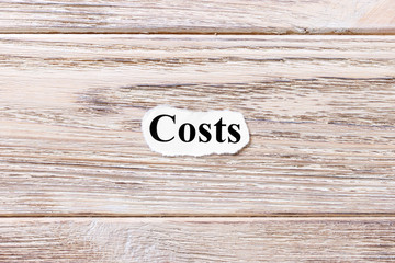 costs of the word on paper. concept. Words of costs on a wooden background