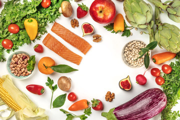 Vibrant fresh food, vegetables, fruits, legumes, fish on white